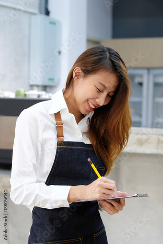 Young asian barista taking order at coffee cafe with smiling face, food and drink business concept - 188056144