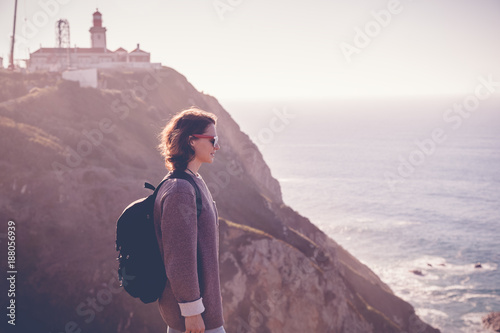 young beautiful woman tourist with a backpack, against the backdrop of Cape Cabo da Roca, portugal, Atlantic coast. Picture with retro toning