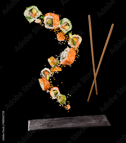 Flying pieces of sushi with wooden chopsticks and stone plate, isolated on black background. - 188065738
