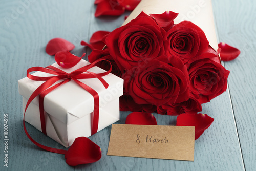 gift box with red roses bouquet for 8 march on blue wood table