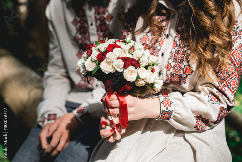 Fotobehang Gerbera fiance and the bride hold in hand wedding bouquet of biege and red roses.