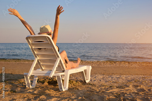 Relaxing at the beach in the evening, backside view. Rear view woman on chaise longue spreading hands wide.