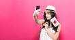 Traveling young woman holding a camera with Japanese flag on a solid background
