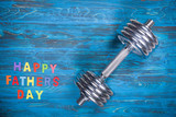 Happy Father's Day concept with dumbbell on wooden background