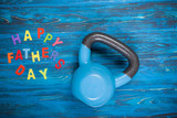 Happy Father's Day inscription with kettlebell on wooden table