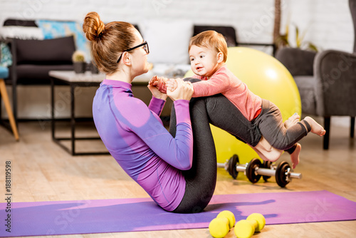 Obraz na płótnie Young mother in sportswear doing exercise lifting with legs her baby son on the mat at home