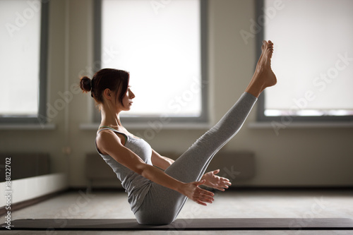Fotobehang School de yoga Young sporty woman doing yoga stretching exercise sitting in gym near bright windows