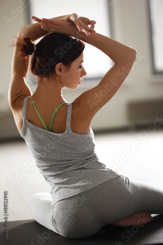 Wall mural Young sporty woman doing yoga stretching exercise sitting in gym near bright windows