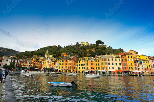 Fotobehang Liguria Colorful buildings on the promenade of Portofino with boats floating in the marina and blue sky background