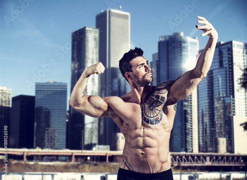 Fridge magnet Handsome muscular tattooed man posing on background of skyscrapers.