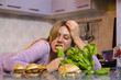 Humor concept, diet, sad young woman biting lettuce, while looking at burgers on kitchen stand