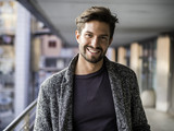One handsome young man in urban setting in European city, standing and smiling to camera happy - 188132529