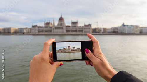 Foto Murales Smartphone held by woman hands. Photo of Budapest parliament building on the smartphone screen, taken from riverbanks of Danube river in BudaPest, Hungary