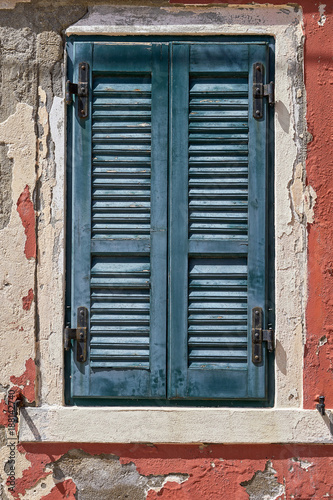 Foto Murales Window with closed old green green shutter on red wall. Italy, Venice, Burano island.