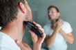 Leinwanddruck Bild - Man shaving beard using electric trimmer shaver. Male beauty grooming concept. Home lifestyle young person looking at bathroom mirror trimming hair on neck.