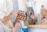 Woman in bathroom applying contour bronzer on brush - 188154531