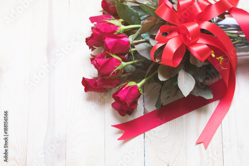 Red rose on wood background with copy space.