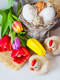 Czech traditional easter decoration - white eggs in a basket, wooden chichen and tupil flowers - 188159705