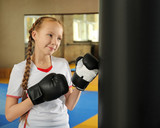 Cute little girl in boxing gloves indoors
