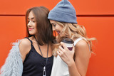 Two happy hipster girls with coffee near color wall outdoors
