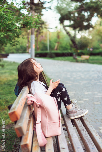 little girl with a smartphone sitting on a bench