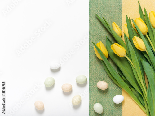 Yellow tulips with colorful eggs over linen tablecloth. Easter background. Top view. Copy space.