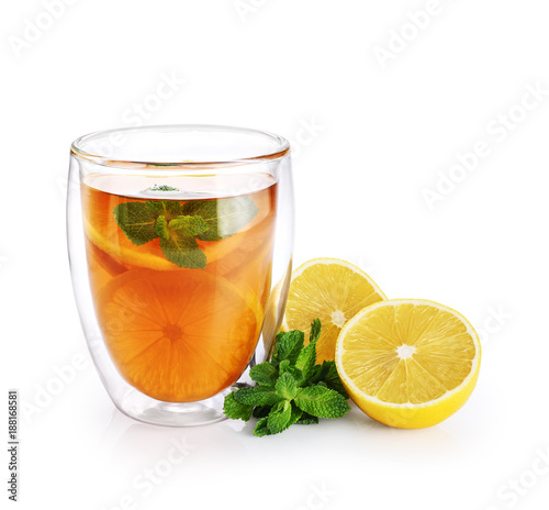 Hot tea with mint and lemon in a glass with double walls isolated on white background.