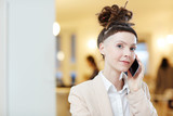 Confident businesswoman with smartphone talking to one of clients and looking at camera - 188174125