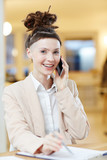 Pretty businesswoman in formalwear looking at camera while phoning and planning work - 188174146