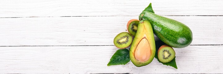 Avocado and kiwi on a wooden background. Top view. Free space for your text.