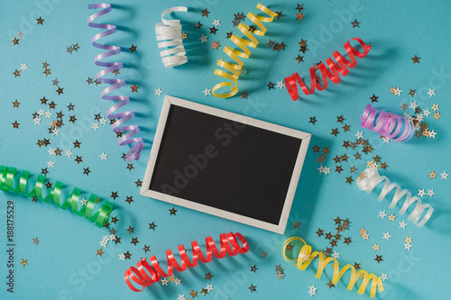 Foto Murales Colorful party streamers, gold little stars and blackboard for text on blue backgrond. Party or birthday concept.