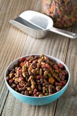Heap of dry pet food in blue plastic bowl