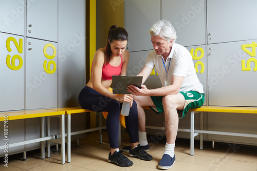 Poster Mature trainer showing one of his trainees her results and discussing them
