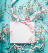 Blank white greeting card with pink ribbon on little white flowers at turquoise blue background, top view, mock up. Pastel color