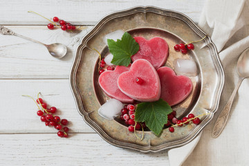 Homemade ice cream of red currant in shape of heart and on vintage dish and wooden background. Top view. Frozen drinks.