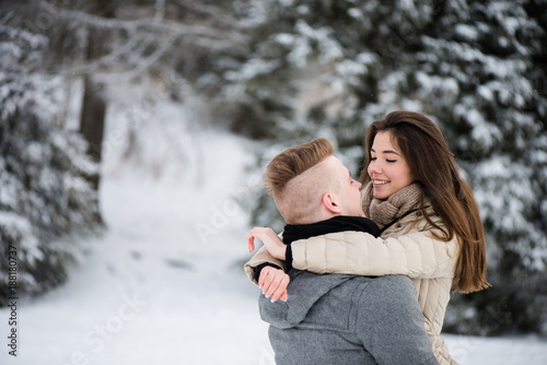 Teen couple romancing in winter forest