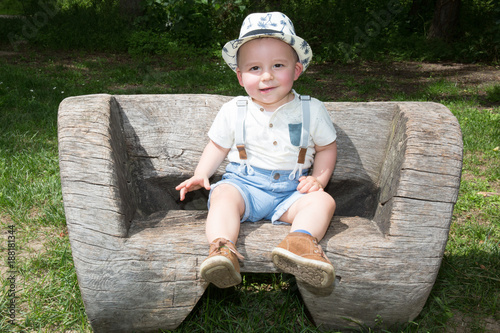 Foto Murales Cute kid boy on the bench in the park in a sunny summer day