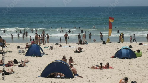 tourists and beach goers on mainbeach at surfers paradise in queensland, australia
