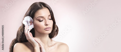 Foto Murales Young and healthy woman with light make-up and Orchid flower in her hair on light pink background.