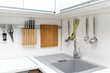 white glossy kitchen interior design with hanging utensils