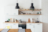 Modern new light interior of kitchen with white furniture and dining table. - 188191506
