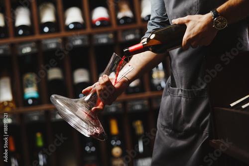 Bartender pours red wine in transparent vessel in cellar © Ilshat