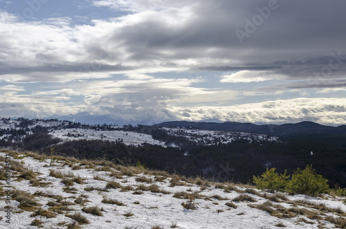 Majestic view of cloudy sky, winter mountain, snowy glade, residential district, conifer and deciduous forest from Plana mountain toward Rila mountain, Bulgaria, Europe - 188194531