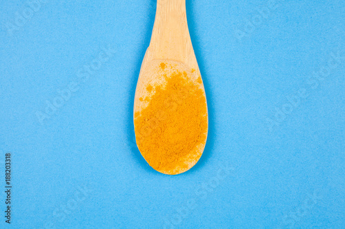Top view on yellow powder spices in wooden spoon on blue background