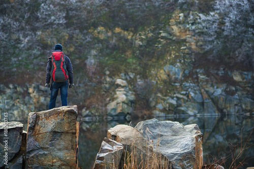 Traveler stands on granite stones amidst a calm lake. Back view © sanechka