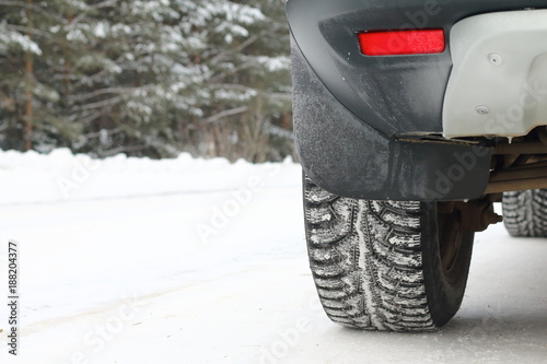 A car is standing by the side of the road in the winter forest. Winter tires. - 188204377