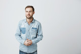 Portrait of puzzled european male wears fashionable denim clothes, keeps hands in together, raises eyebrow in bewilderment, has to make difficult life choice, looks confused - 188204785