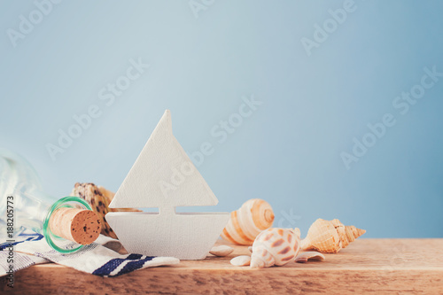 Fototapeta Some elements of vacation theme, shell, botle and toy ship on blue backround, copy space