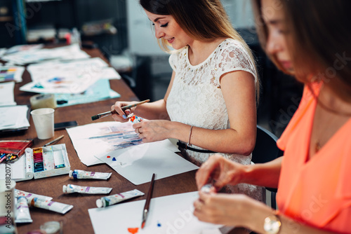 Female friends attending painting workshop together