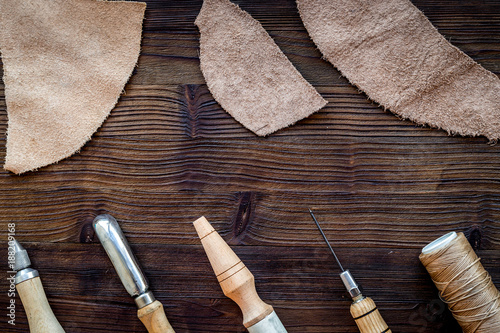 Foto Murales Leather craft accessories. Tools and matherials on dark wooden b